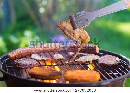 Grilled meat on bbq. Barbecue lunch in the garden. Grill tools. German sausage and steak for outdoor dinner. - stock photo