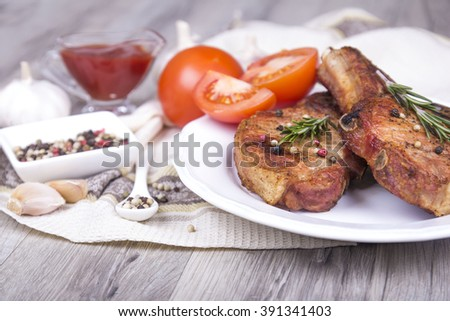 Grilled meat (pork) steaks on cutting board with tomatoes, garlic, peppers mix, and rosemary on wooden cutting board   - stock photo