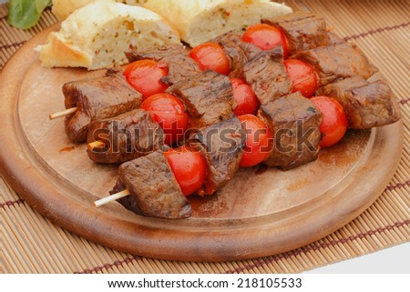 Grilled meat skewers with salad and vegetables on a wooden cutting board - stock photo