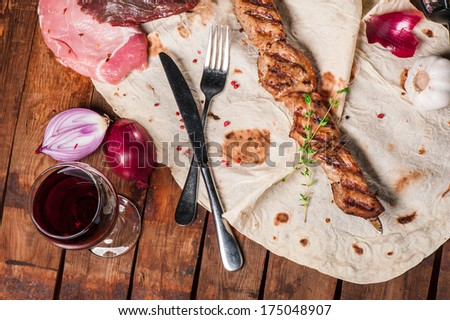 Grilled meat with spices and thyme on skewer lays on pita - stock photo