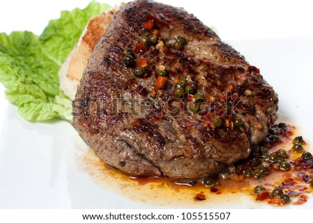 Grilled meat with vegetable sauce. White bread and green salad - stock photo