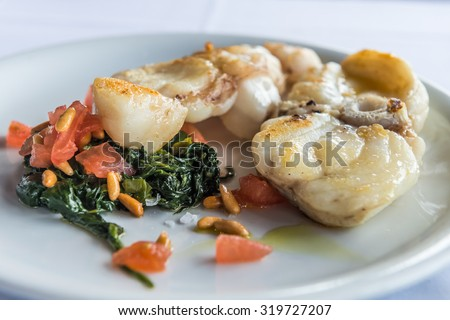 Grilled monkfish garnished spinach with cedar nut and tomatoes - stock photo