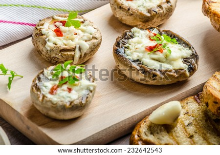 Grilled mushrooms stuffed with blue cheese and chilli and garlic toast - stock photo