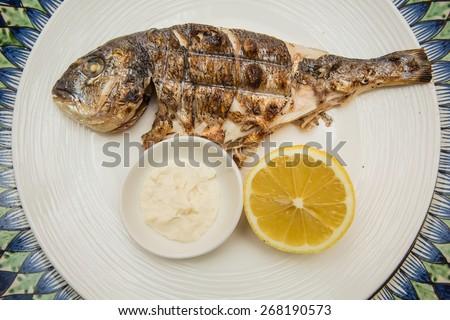 Grilled organic dorada fish with lemon on white dish - stock photo