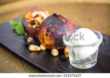 Grilled peaches with nuts and ice-cream. Dessert - stock photo