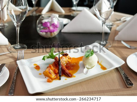 Grilled pineapple cooked in syrup, dessert on restaurant table - stock photo