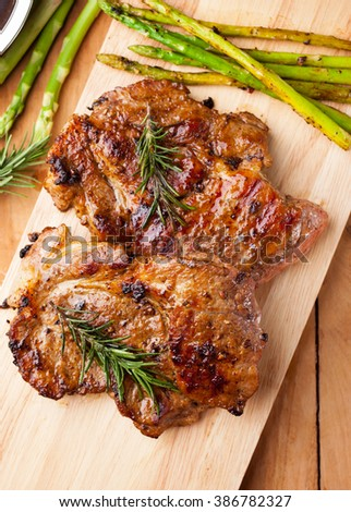 grilled pork chop with asparagus and rosemary on wooden board - stock photo
