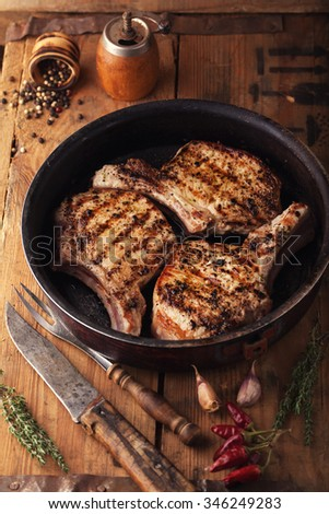 Grilled pork chop with spices in a frying pan on a wooden box - stock photo