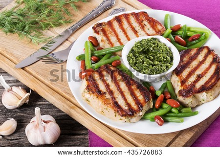 grilled pork chops on a white dish - stock photo