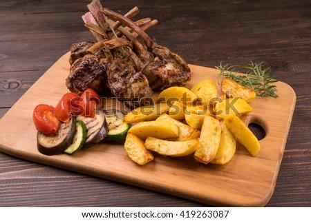 Grilled Pork Rib , Roast potatoes on wooden board with vegetables and potatoes . Pork ribs on wooden board with vegetables and potatoes . - stock photo