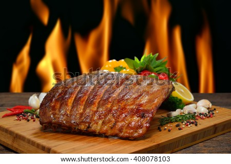 Grilled pork ribs and various vegetables on a chopping wood - stock photo
