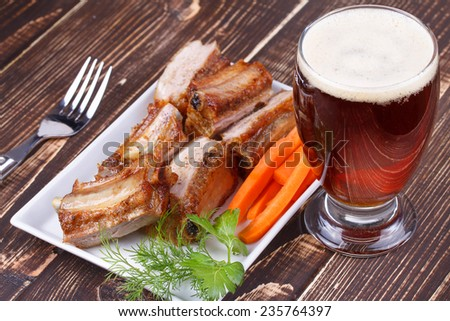 Grilled pork ribs, fresh carrot and glass of beer on wooden background - stock photo