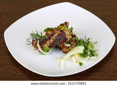 Grilled pork ribs with onion, parsley and rosemary - stock photo