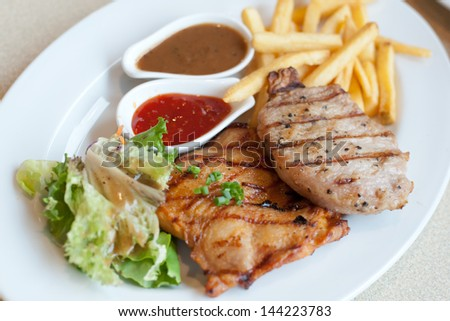 Grilled pork steak and Chicken steak, French fries and vegetables - stock photo