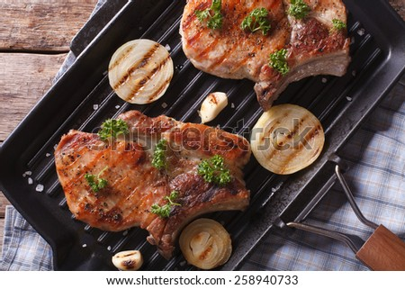 Grilled pork steak with onion in a pan grill close-up, horizontal view from above - stock photo