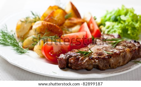 Grilled pork steak with vegetables and roasted potatoes - stock photo