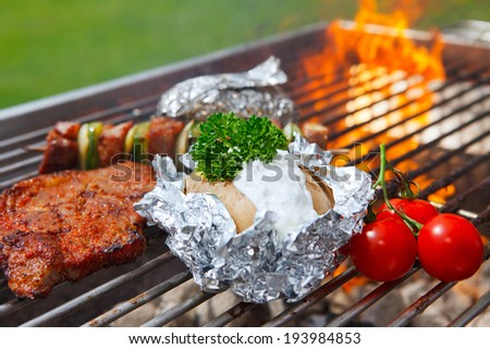 grilled potato with flames in background - stock photo