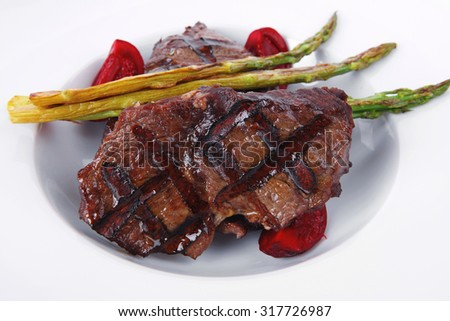 grilled red beef pork meat barbecue steak fillet with asparagus and hot pepper served on deep plate isolated on white background - stock photo