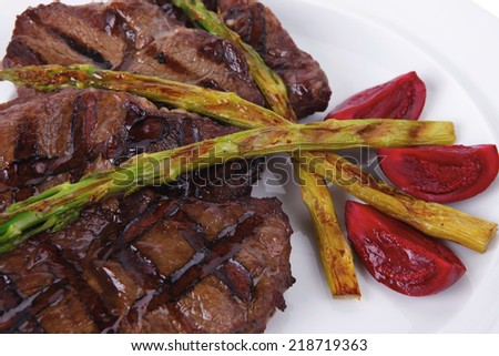 grilled red beef pork meat bbq steak fillet with asparagus and hot pepper served on plate isolated on white background - stock photo