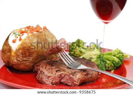 Grilled rib eye steak with baked potato and broccoli.  Isolated on white background. - stock photo