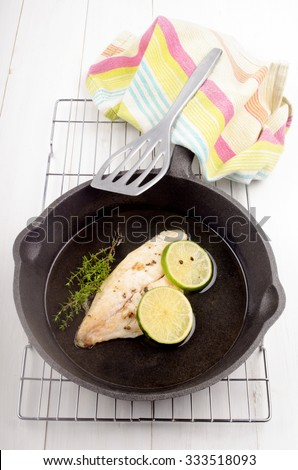 grilled river cobbler with lime slice in a cast iron pan - stock photo