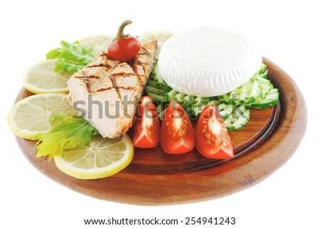 grilled salmon and greek cheese on wooden plate - stock photo