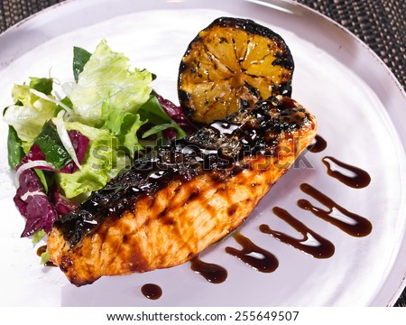 grilled salmon and lemon, with fresh salad. Selective focus - stock photo