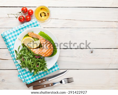 Grilled salmon and white wine on wooden table. Top view with copy space - stock photo