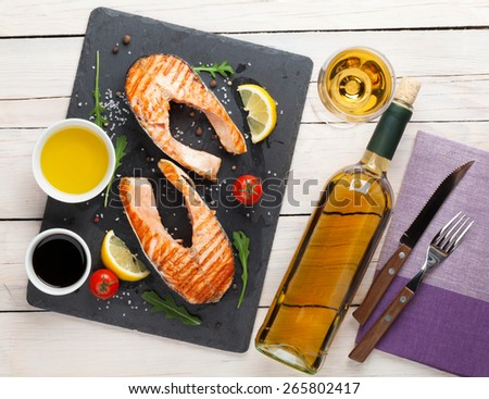 Grilled salmon and whtie wine on wooden table. Top view - stock photo