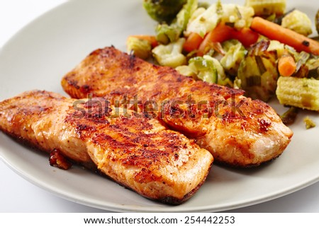 Grilled salmon fillet with fried vegetables on a plate - stock photo
