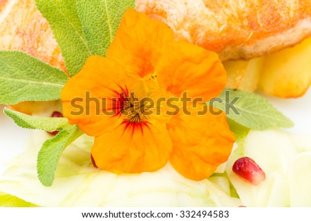 Grilled salmon fillet with sliced cucumbers and roasted potatoes. With fresh flower on top as a decoration. Macro. Photo can be used as a whole background. - stock photo