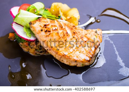 Grilled salmon fish fillet with fresh tomatoes, radish, cucumbers on a plate, selective focus - stock photo