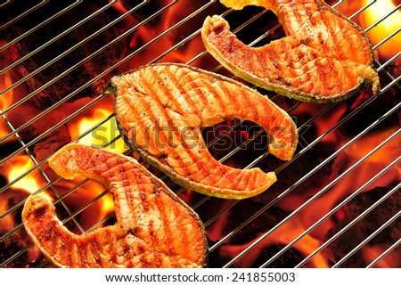 Grilled salmon on the flaming grill - stock photo