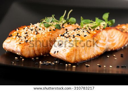 Grilled salmon, sesame seeds  and marjoram on a black plate. Studio shot - stock photo