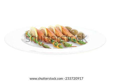 grilled salmon slices with asparagus lemon green olives and fried orange peel on big plate isolated over white background - stock photo