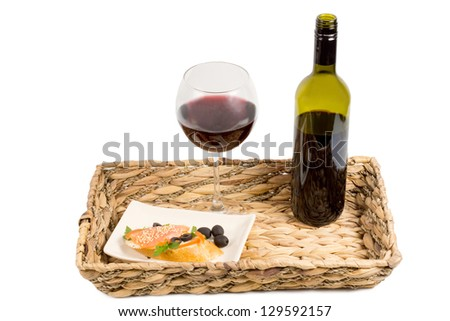 Grilled salmon steak and red wine in a glass and unlabelled bottle served on a rustic woven tray isolated on white - stock photo