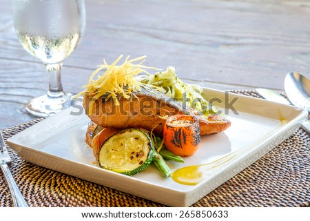 grilled salmon steak served with pasta and vegetables in a small outdoor restaurant - stock photo