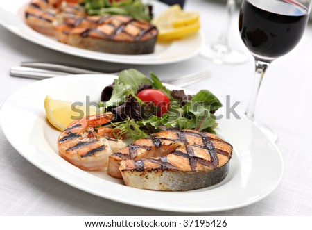 Grilled salmon steak with shrimps and fresh summer salad mix - stock photo