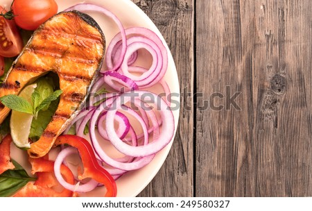 Grilled salmon steak with sliced onion and tomatoes on old wooden table top view at left side - stock photo