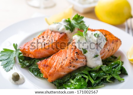 Grilled Salmon Steak  with Spinach, Tartare Cream and Lemon Wedges - stock photo