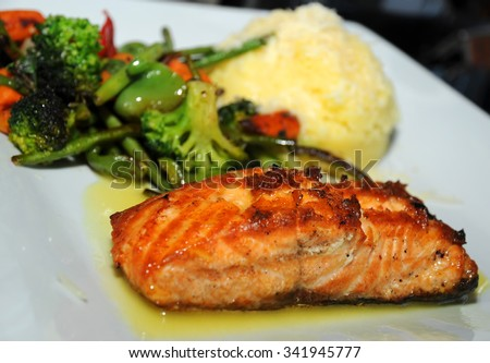 Grilled Salmon with cooked Vegetables and mashed potatoes on a white plate. Selective focus   - stock photo