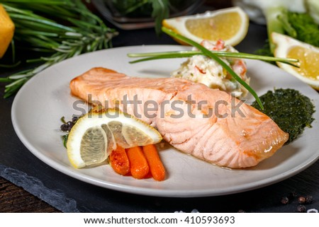 Grilled Salmon with lemon, herbs and pesto. Red carrots. Potato salad. - stock photo