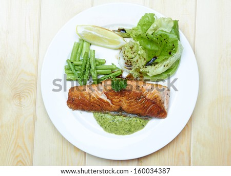 Grilled salmon with Salsa Verde, asparagus, pea, yellow peppers, carrots and spring onions on white plate  - stock photo
