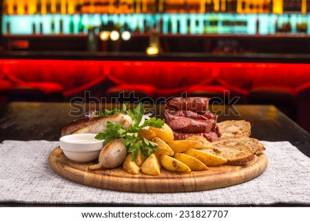 Grilled sausage with potatoes and bread on wooden board on the table - stock photo