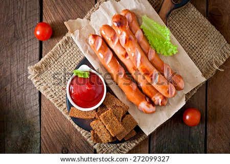 Grilled sausages, crackers and beer on a wooden background in rustic style. Top view - stock photo