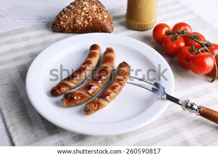 Grilled sausages on plate with bread and cherry tomatoes on table close up - stock photo