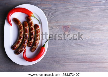 Grilled sausages on plate with chili pepper on table close up - stock photo