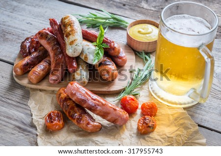 Grilled sausages with glass of beer - stock photo