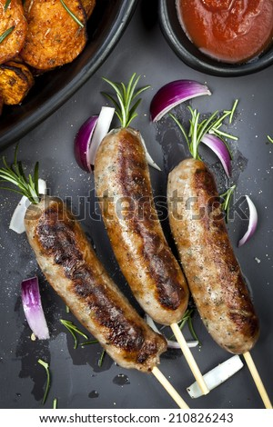 Grilled sausages with rosemary, sweet potato fries, and red onion. - stock photo