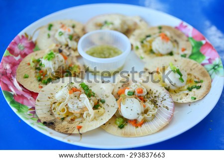 Grilled scallops topped with butter, garlic and onion - stock photo